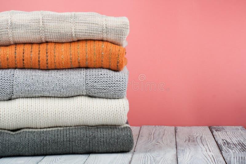 Suéteres hechos punto de las lanas La pila de invierno hecho punto, otoño viste en rojo, fondo de madera, suéteres, géneros de pu imagen de archivo