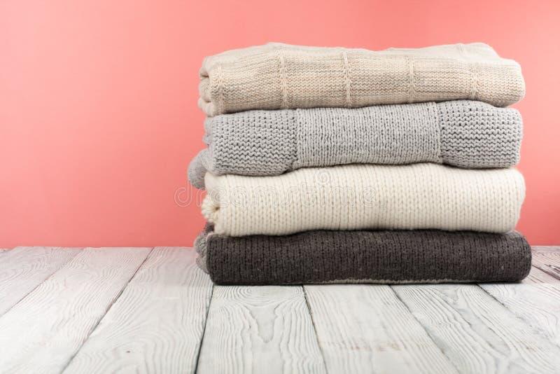 Suéteres hechos punto de las lanas La pila de invierno hecho punto, otoño viste en rojo, fondo de madera, suéteres, géneros de pu fotografía de archivo libre de regalías