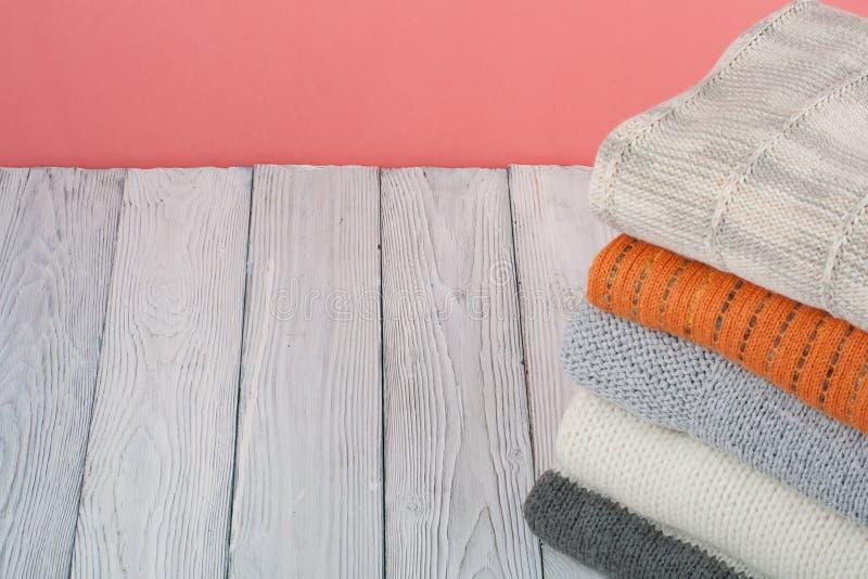 Suéteres hechos punto de las lanas La pila de invierno hecho punto, otoño viste en rojo, fondo de madera, suéteres, géneros de pu imagen de archivo libre de regalías