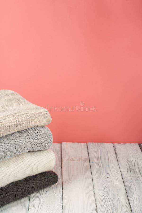 Suéteres hechos punto de las lanas La pila de invierno hecho punto, otoño viste en rojo, fondo de madera, suéteres, géneros de pu foto de archivo