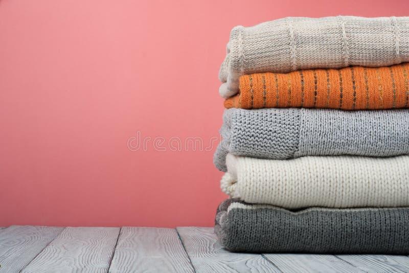 Suéteres hechos punto de las lanas La pila de invierno hecho punto, otoño viste en rojo, fondo de madera, suéteres, géneros de pu imagenes de archivo