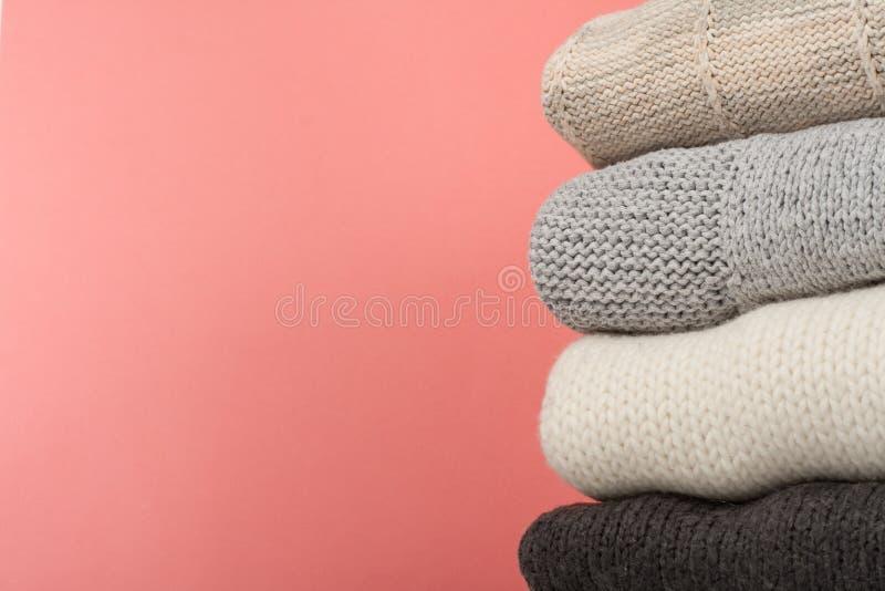 Suéteres hechos punto de las lanas La pila de invierno hecho punto, otoño viste en rojo, fondo de madera, suéteres, géneros de pu imágenes de archivo libres de regalías