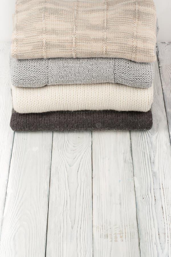 Suéteres hechos punto de las lanas La pila de invierno hecho punto viste en el fondo de madera, suéteres, géneros de punto, espac foto de archivo