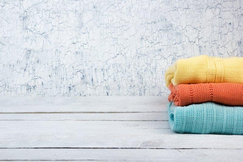 Suéteres hechos punto de las lanas La pila de verano hecho punto viste en el fondo de madera, suéteres, géneros de punto, espacio foto de archivo libre de regalías