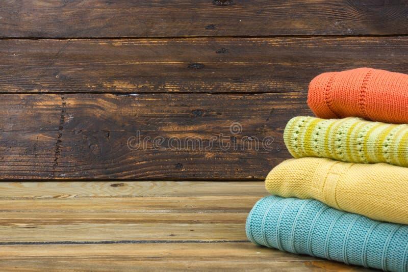 Suéteres hechos punto de las lanas La pila de verano hecho punto viste en el fondo de madera, suéteres, géneros de punto, espacio fotografía de archivo