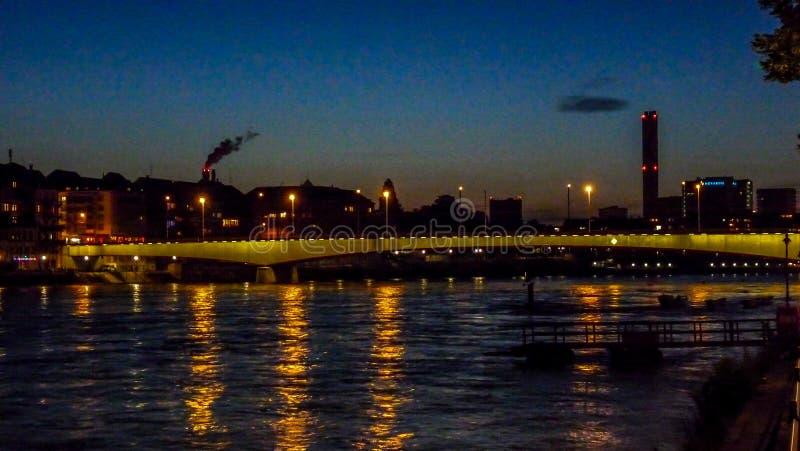 Suíça, Basileia, CONSTRUÇÕES ILUMINADAS por Rhine River CONTRA imagem de stock royalty free