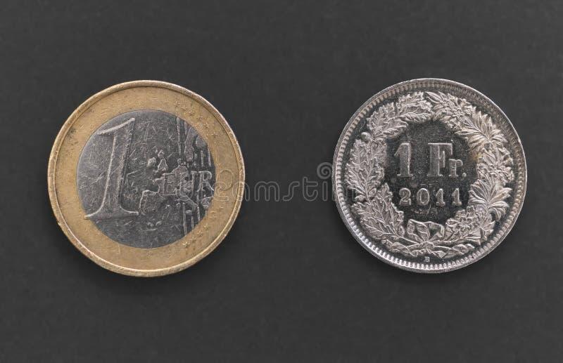 Suíço um Franc Coin e 1 euro- moeda fotos de stock royalty free