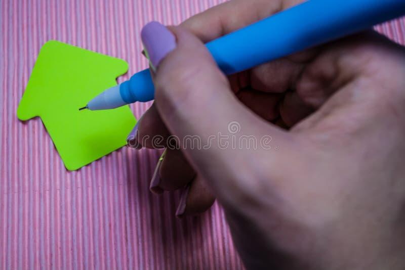 Su fondo rosa luminoso monofonico la penna blu insolita con la testa dei cervi Autoadesivi vicini di bugia, carta per appunti uff fotografia stock libera da diritti