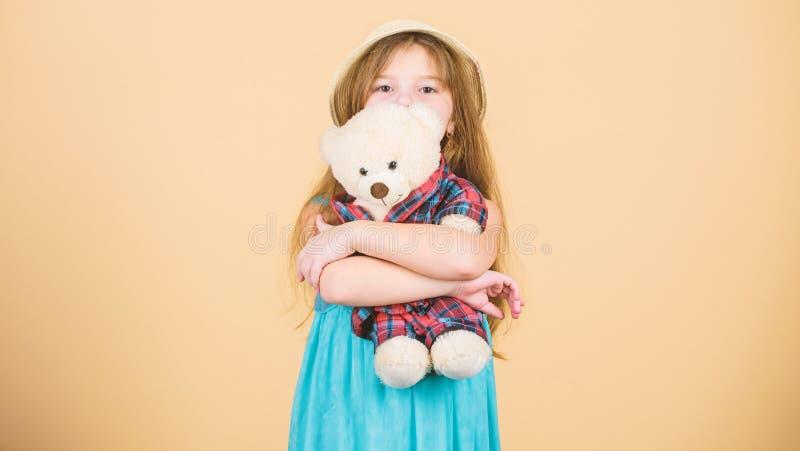 Su juguete preferido Ni?a que sostiene el juguete suave Juguete de abrazo del oso de peluche del peque?o ni?o Ni?o adorable de la fotos de archivo libres de regalías