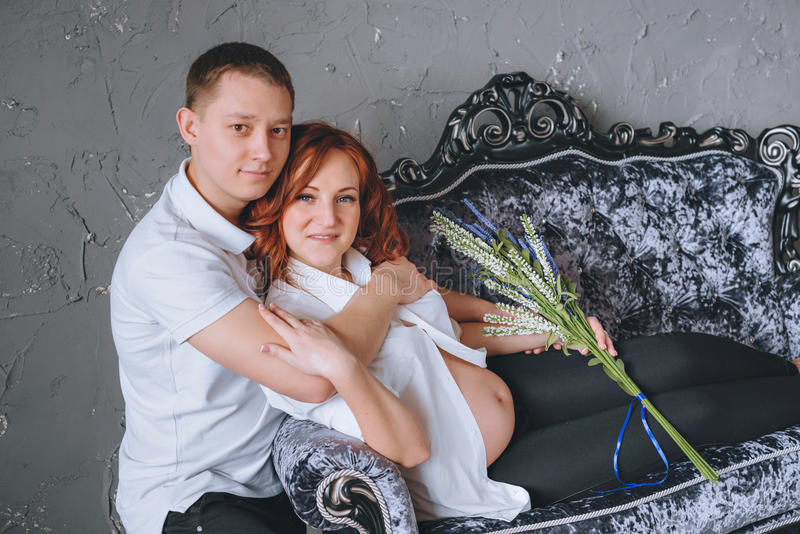 Su marido que abraza a la mujer embarazada en el sofá gris con lavanda a disposición foto de archivo libre de regalías