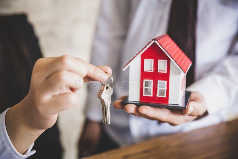 Su nueva casa, llave de la casa de la tenencia del agente inmobiliario a su cliente despu?s de firmar el acuerdo de contrato en o fotografía de archivo libre de regalías