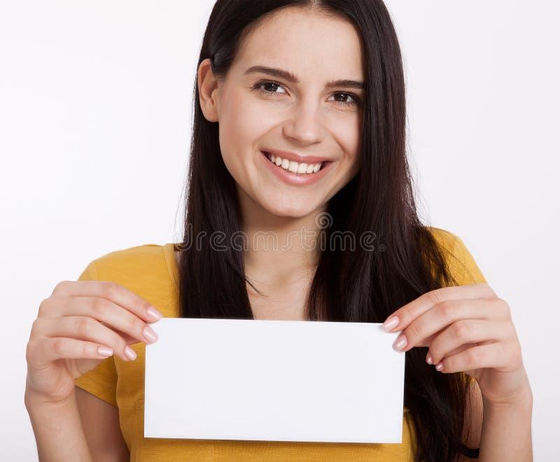 Su texto aquí Mujer bastante joven que lleva a cabo al tablero en blanco vacío Retrato del estudio en el fondo blanco Maqueta par fotografía de archivo libre de regalías