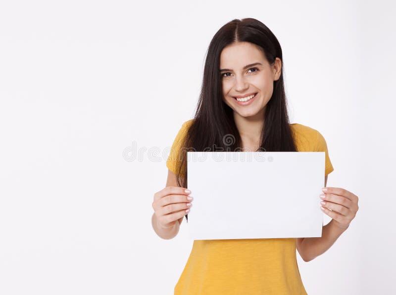 Su texto aquí Mujer bastante joven que lleva a cabo al tablero en blanco vacío Retrato del estudio en el fondo blanco Maqueta par imagen de archivo