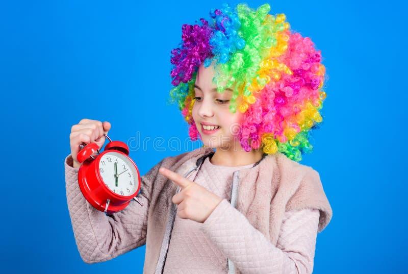Su tiempo de reclinación Niña feliz con el pelo colorido de la peluca que señala en el despertador por el tiempo exacto Mida el t imágenes de archivo libres de regalías