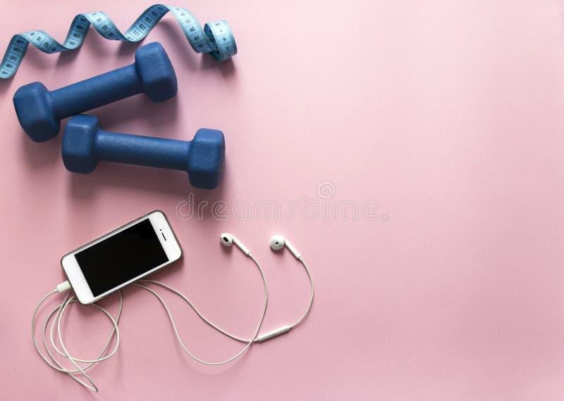 Su un blu e su un centimetro volante delle teste di legno del fondo di rosa calcoli la luce morbida dello smartphone del telefono immagine stock