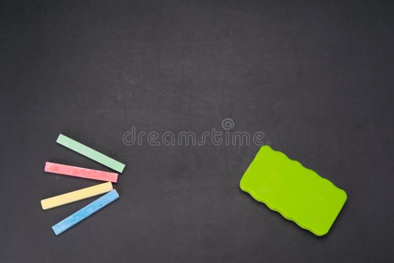 su un bordo nero è di un gesso colorato multi per il disegno e una spugna per cancellare fotografia stock libera da diritti