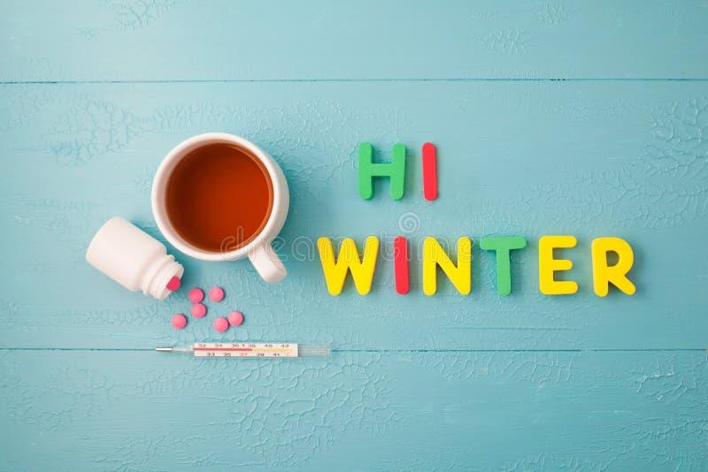 Su un fondo blu un termometro, compresse, un tovagliolo corrugato un l'inverno dell'iscrizione ciao e tè Vista superiore fotografie stock