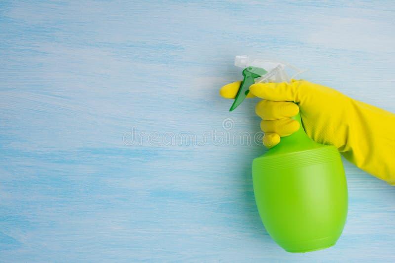 Su un fondo blu, una mano in un guanto giallo tiene una bottiglia verde per i liquidi di spruzzatura, c'è un posto per la scrittu fotografia stock libera da diritti