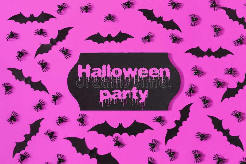 Su un fondo brillantemente viola, i ragni ed i pipistrelli decorativi di Halloween sono presentati Nel centro è una placca nera fotografia stock libera da diritti