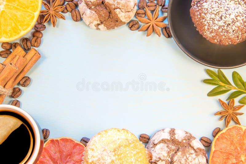 Su un fondo del blu i biscotti decomposti con la tazza di caffè dei bigné hanno affettato le arance della salsa della cannella de fotografia stock libera da diritti