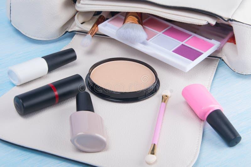 Su un fondo leggero, da una borsa cosmetica bianca, dagli oggetti sparsi per il manicure e da un trucco, ombretto colorato, spazz fotografia stock libera da diritti