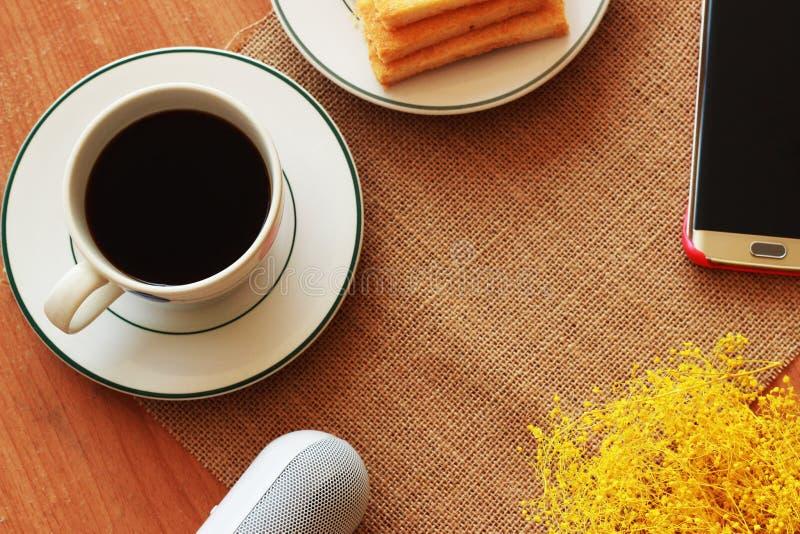 Su un fondo marrone c'è un caffè nero, un pane croccante e immagini stock