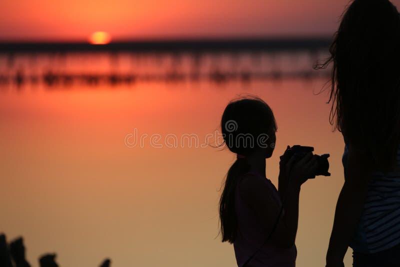 Su un lago di sale due le ragazze sono offuscate contro lo sfondo dell'orizzonte, fotografato al tramonto fotografia stock