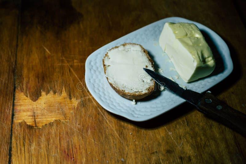 Su un piatto, unga un pezzo di pane con olio immagini stock