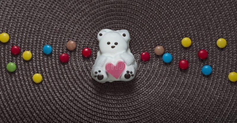 Su un tovagliolo nel centro di un dolce come un orso con un cuore in sue mani accanto ad una caramella colorata fotografia stock libera da diritti