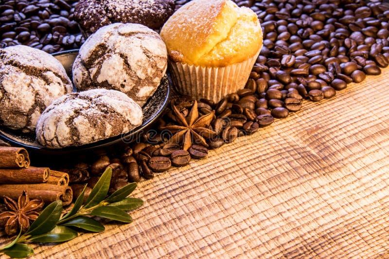 Su una tavola di legno c'è una tazza di caffè nero accanto ad un piatto dei biscotti del cioccolato spruzzati con lo zucchero in  immagini stock libere da diritti