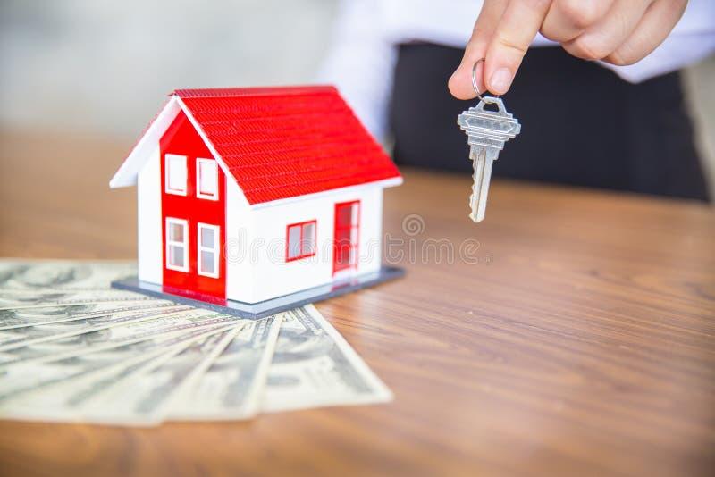 Sua casa nova, mãos da mulher guardando uma casa e uma chave modelo Hipoteque a casa movente ideal do seguro patrimonial e o conc fotografia de stock
