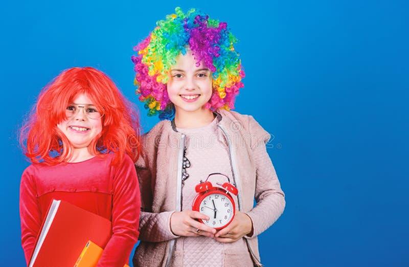Sua hora de comemorar Meninas que vestem as perucas loucas que v?o ? noite do partido Crian?as bonitos com o cabelo extravagante  fotografia de stock