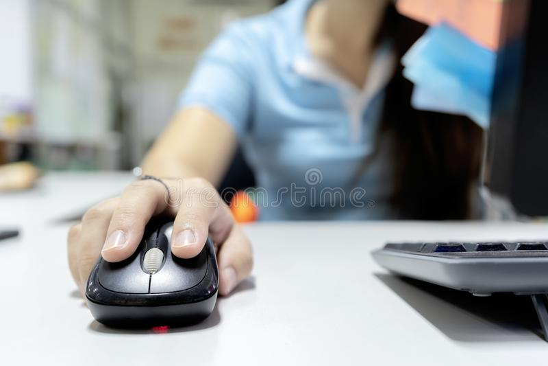 Sua mão está guardando o rato para comandar o computador fotografia de stock