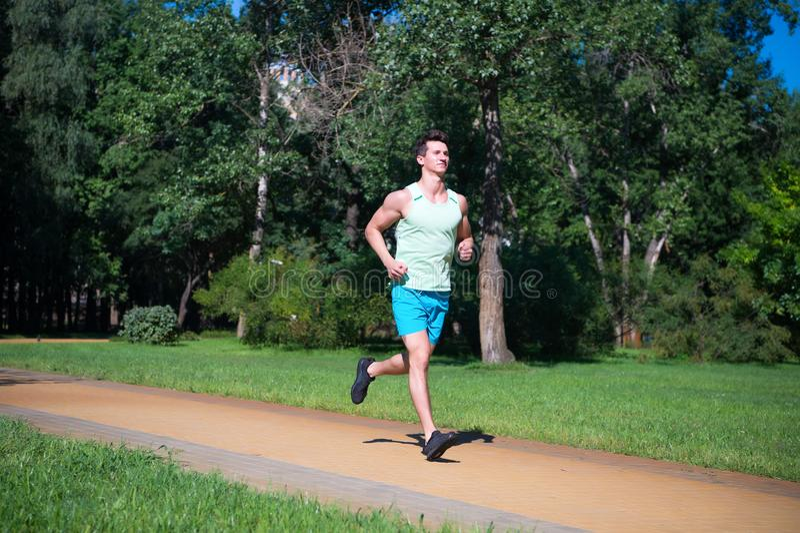 Sua melhor velocidade O basculador do homem corre no fundo da natureza do dia ensolarado do parque Equipe o treinamento, prepare  imagens de stock