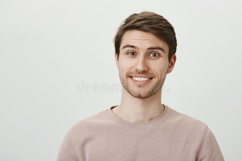 Sua vida é inacreditável Estudante masculino europeu considerável interessado com cerda que sorri alegremente ao levantar foto de stock