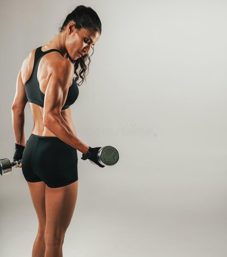 Suando o peso de levantamento do atleta fêmea imagens de stock