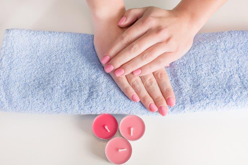 Suavemente manos de la mujer con la manicura rosada en clavos imagen de archivo
