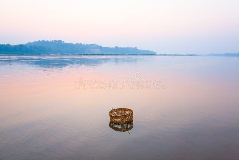 Suavemente río hermoso en la salida del sol, cesta de bambú para el veg que se lava foto de archivo