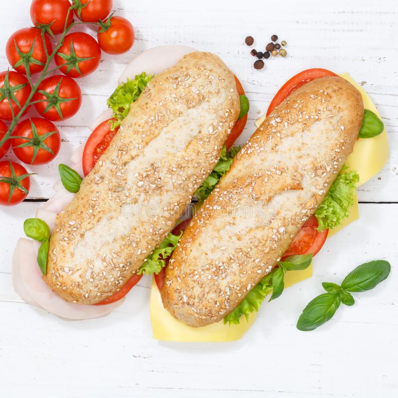 Sub sandwich whole grain grains baguette with cheese and ham fro. M above square on wooden board wood royalty free stock photo