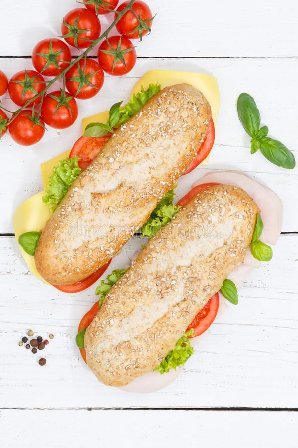 Sub sandwich whole grain grains baguette with cheese and ham fro. M above portrait format on wooden board wood royalty free stock photography