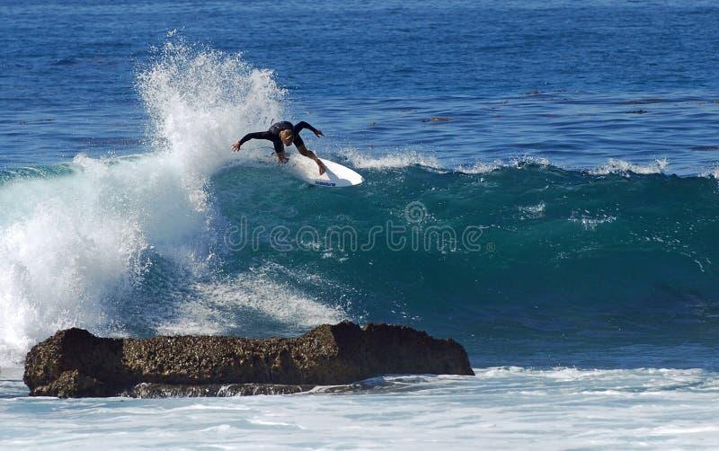 Suba al montar a caballo de la persona que practica surf en una onda en el Laguna Beach, CA imagenes de archivo