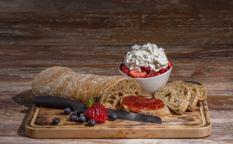 Suba con las partes del pan y de la mermelada de fresa deliciosa en la tabla de madera fotos de archivo libres de regalías