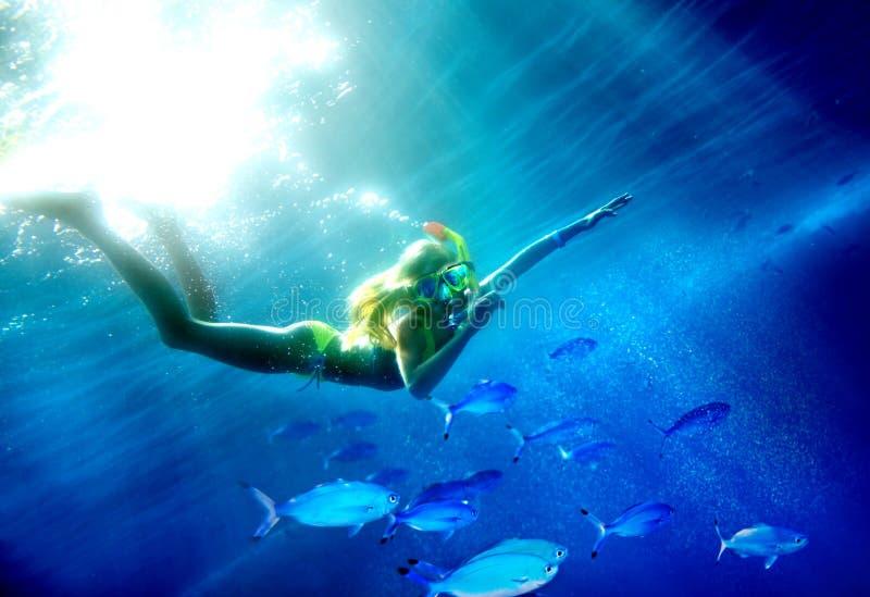 Subaqueo del bambino con i pesci del corallo del gruppo. immagine stock