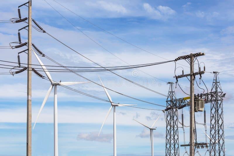 Subestação de alta tensão do pilão da corrente elétrica com energias eólicas renováveis das turbinas eólicas imagens de stock royalty free