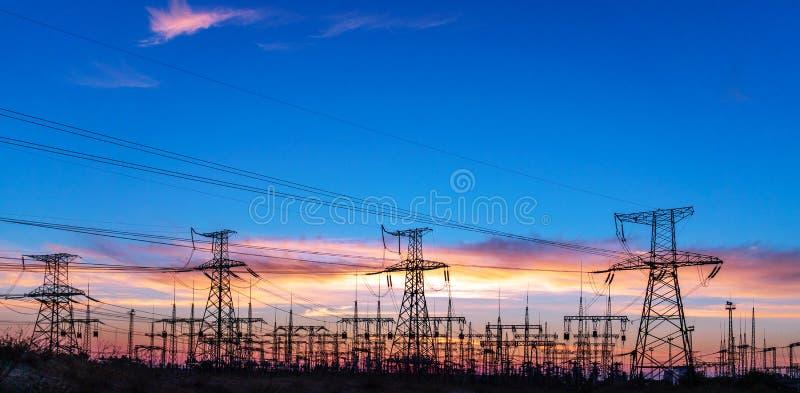Subestación eléctrica de la distribución con las líneas eléctricas y los transformadores, en la puesta del sol imagen de archivo