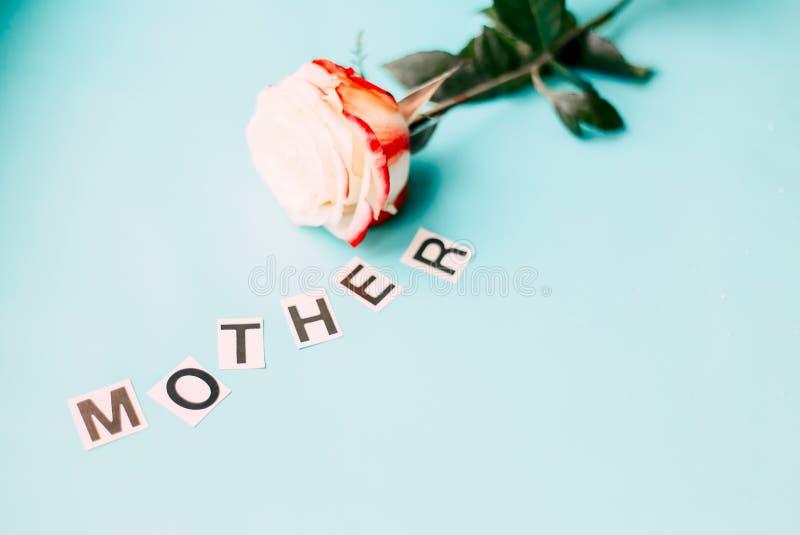 subió para la madre, pone letras a la madre en fondo azul foto de archivo libre de regalías