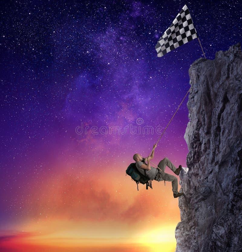 Subida del hombre de negocios una montaña para conseguir la bandera Meta de negocio del logro y concepto difícil de la carrera fotos de archivo libres de regalías