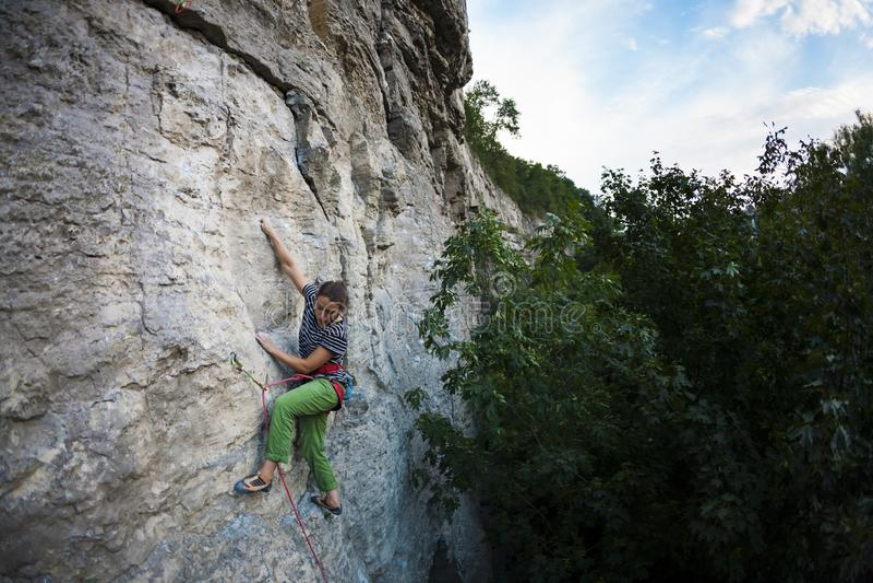 Subidas de la muchacha de los deportes en la roca imagen de archivo