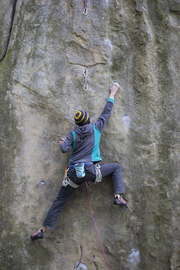 Subidas del atleta en roca con la cuerda fotos de archivo