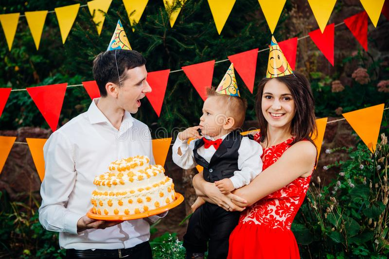 Subject children`s birthday party, food and sweets. A young family celebrates one year of son. Dad is holding a big cake, mom is stock images